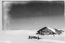 Old, damaged vintage retro style tundra landscape black and white photo. Wooden house with well covered with snow in the front. Lots of age marks, letters, scratches placed on the film tape surface.