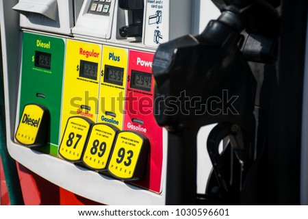 Old dangerous combustible petrol chemical gas. At the Gas station. Filling up gasoline at the gas pump. 87 octane , 89 octane , or 93 octane. With gas pump handle ready to fill up the tank