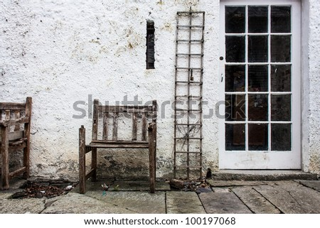 Old decayed chair and vine rack in backyard