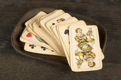 Old deck of cards with joker on a wooden plate