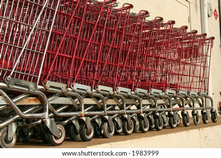 Old decommissioned grocery carts stacked against a wall.  Carts closest are focused while others are out of focus due to shallow depth of field.