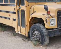 Old decommissioned school bus with a flat tire