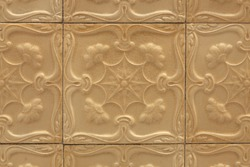 old decorative and ornamental exterior wall surface tiles in shades of light brown with embossed shapes and floral motifs, monochrome pattern. Glazed ceramic tiles pattern for background texture.