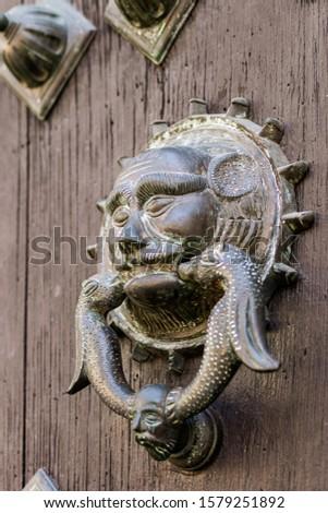 Old decorative brass knocker at a door of Merida Cathedral (Catedral de Yucatan) in Merida, Yucatan, Mexico.