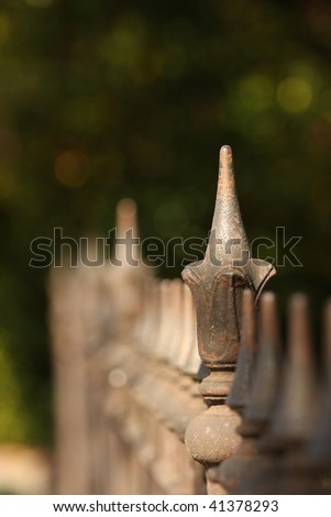 Old decorative iron fence in late afternoon light, with shallow depth of field receding into distance, with green trees behind.