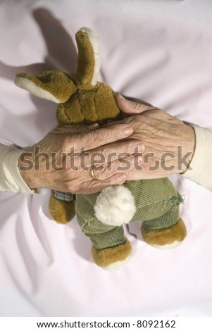 Old demented person with stuffed rabbit
