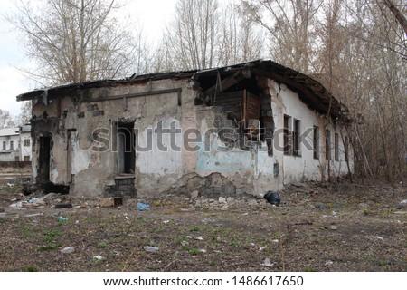 old destroyed building with broken broken broken glass in the Windows non-residential premises house with dangerous debris falls #1486617650