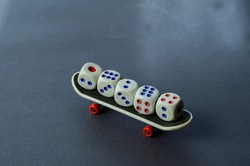 Old dice and finger skate on a gray background. Five random white dice on top of the mini skateboard. Side view. Selective focus.