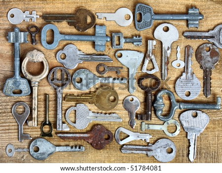 Old different keys on wooden background