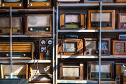 Old different retro radios arranged on an antique store shelves.