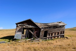 old dilapidated abandoned  farm house on a prairie landscape with missing windows or doors