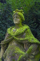 Old, dilapidated and moss-covered statue of Queen in Italian park.