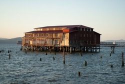 Old dilapidated building on piers above water