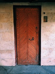 old dilapidated wooden door of an abandoned house closed by a rusty lock and not used for a long time