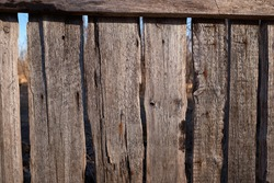 Old dilapidated wooden fence with rusty nails against the blue sky. Village background. Silence and desolation.