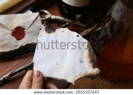 old dirty and burnt sheet of paper in hand, on which nothing is written. based on the novels of J.K. Rowling on Harry Potter Stock fotó ©