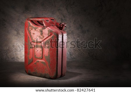 Old, dirty and rusty red jerry can fuel container.