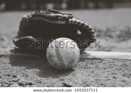 Old dirty baseball with glove on dirt field brings back nostalgia of sports memories for ball player in black and white.