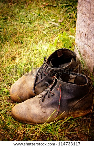 old dirty boots.old boots worn with scratches and untied shoelaces on grunge background