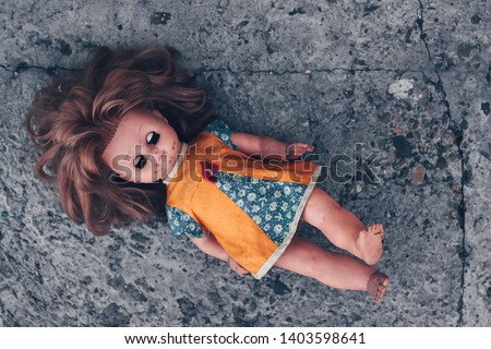 Old dirty doll with her eyes closed on concrete floor. The concept of a bygone childhood, loneliness and abandoned #1403598641