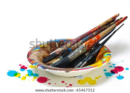 Old dirty painting brushes resting in a colorful plate #65467312