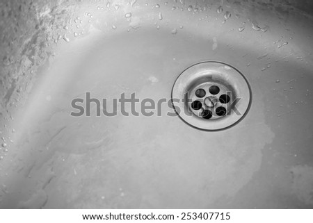 Old dirty sink. Plug hole of a kitchen sink. Black and White image.