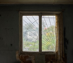 Old dirty window with tattered curtains in old abandoned building interior. Old abandoned car outside