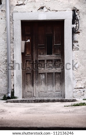 Old dirty wooden door and broken facade with drip installation
