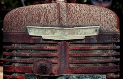 old disused and rusted tractor grill with retro insignia