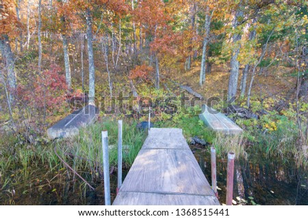 Old dock and boat on small remote lake in Northern Wisconsin with fall trees and fall color on shoreline #1368515441