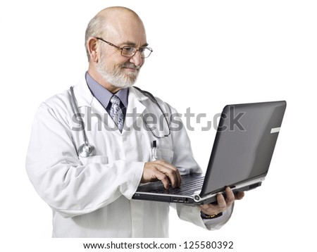 Old doctor using a laptop isolated in a white background