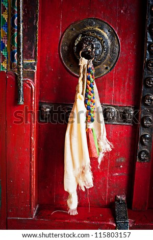 Old door at Buddhist monastery temple decorated with ancient doorknob and tassel. India, Ladakh, Diskit monastery