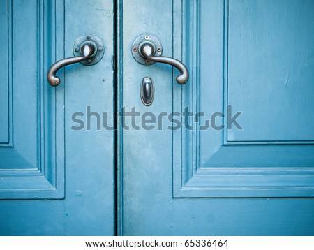 Old Door handles with an old double door painted with blue