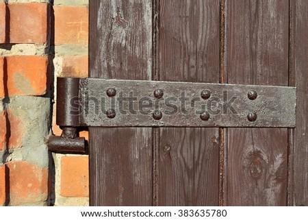 Old door hinge on wooden door closeup