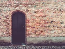 Old door in rustic brick wall, bruges, belgium