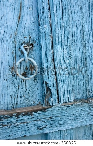 Old door with flaking worn blue paint in an adobe building in a pueblo in northern New Mexico.