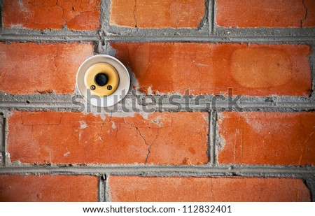 Old doorbell on the brick wall