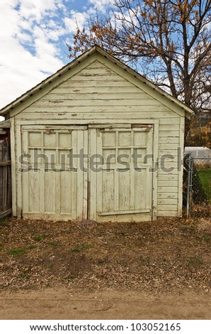Old double doors with boarded up windows on a rarely used garage with a rock in front of the the doors to keep them closed