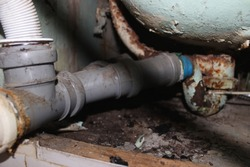 Old drainage pipeline from the bathroom with gray plastic and rusty metal pipes with blue duct tape to repair the plumbing in the bathroom