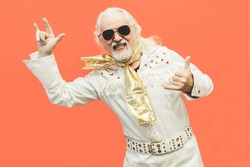 Old dressed up man pensioner who loves rock'n'roll, dancing and having fun on a living coral background - Concept of enjoying life at every age