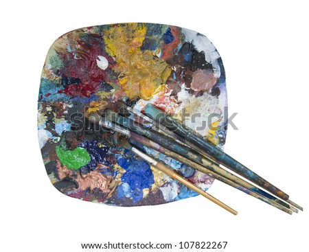 old dried paint and paint brushes on a plate being used as a mixing palette