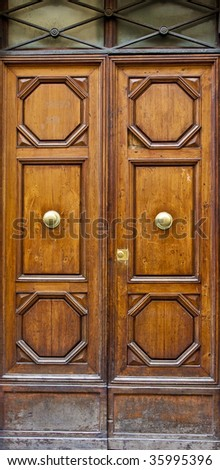 Old dusty doors with ornate carving and brass fixtures