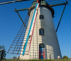 Old Dutch white windmill with blue sky background in Holland
