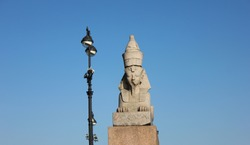 Old egyptian Sphinx on quay with Sphinxes in Saint Petersburg, Russia. Historic city landmark, ancient sphinx statue isolated on empty blue sky background. St Petersburg scenic attraction view