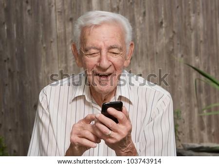 Old elder senior man on mobile smart phone - stock photo