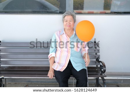 old elder woman holding balloon. asian elderly female relaxing outdoors. senior leisure lifestyle