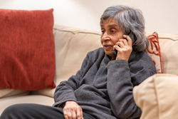 Old elderly, British Asian woman talking on a phone, self isolating during coronavirus outbreak lockdown in UK