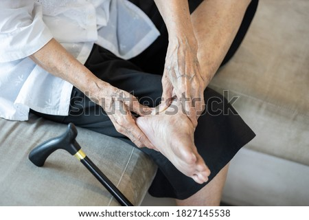 Old elderly with foot injuries,heel pain or ankle diseases,asian senior woman suffer from plantar fasciitis,tendon connecting calf muscles to the heel injury,achilles tendinitis after walk exercising Foto stock ©