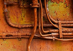 Old electrical cables on a rusty iron wall