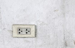 old electrical outlet on grimy white concrete wall, socket panel for plug of household electrical appliances, close up with copy space